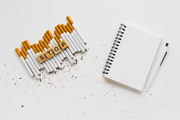 Bovenaanzicht woord met sigaretten en notebook