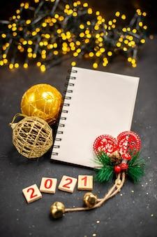 Bovenaanzicht xmas opknoping ornamenten een notebook hout blok kerstverlichting op donkere ondergrond
