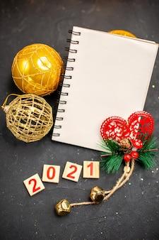 Bovenaanzicht xmas opknoping ornamenten een notebook hout blok op donkere ondergrond