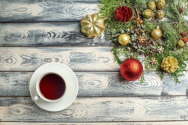 Bovenaanzicht xmas ornamenten een kopje thee spar boomtakken op houten achtergrond vrije ruimte