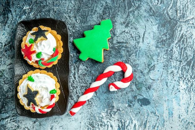 Bovenaanzicht xmas taarten op zwarte plaat xmas candy en xmas tree biscuit op grijze tafel