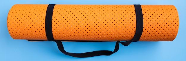 Bovenaanzicht yoga mat op blauwe achtergrond