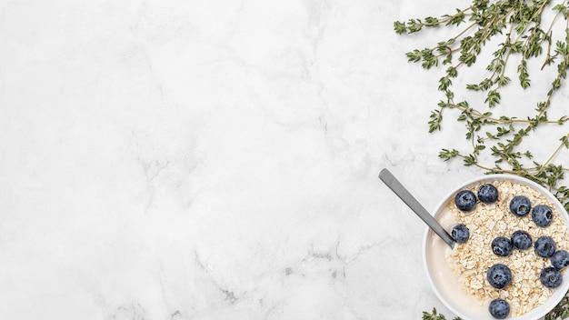 Bovenaanzicht yoghurt met bosbessen en haver met kopie-ruimte