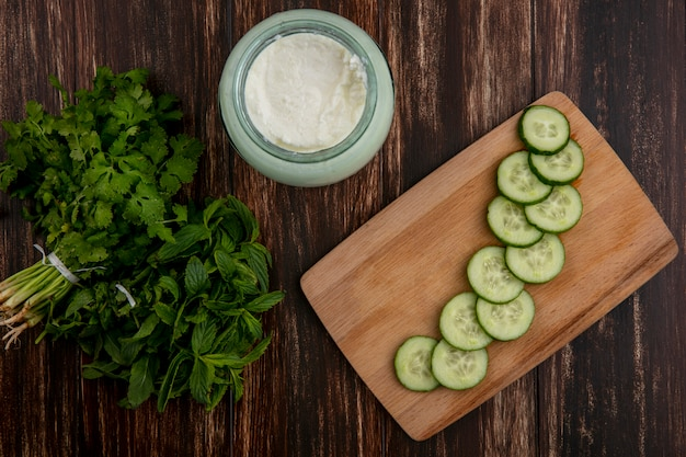 Bovenaanzicht yoghurt met gehakte komkommers op een bord en een bos van greens op een houten tafel