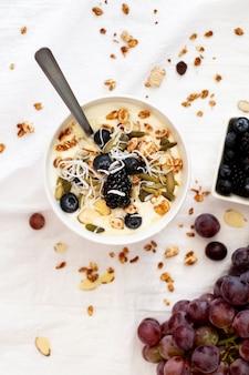 Bovenaanzicht yoghurtkom met fruit en ontbijtgranen
