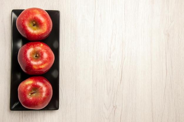 Bovenaanzicht zachte rode appels vers fruit in zwarte pan op wit bureau fruit zachte rijpe verse rode kleur