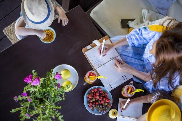 Bovenaanzicht zakelijke vrouwelijke planning maken van aantekeningen ontspannen met twee gelukkige kinderen op zomerterras