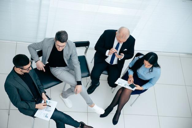 Bovenaanzicht. zakenman die een smartphone gebruikt tijdens een werkvergadering. foto met kopieerruimte