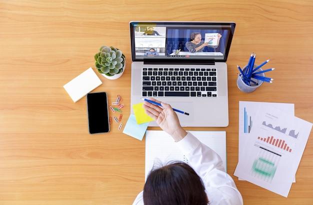 Bovenaanzicht zakenman en zakenvrouw analyse financiële grafiek met videoconferentie onlinevergadering.