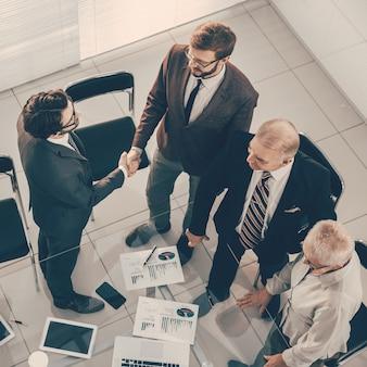 Bovenaanzicht zakenmensen die elkaar begroeten voor de vergadering