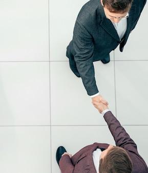 Bovenaanzicht zakenmensen die elkaar ontmoeten met een handdruk