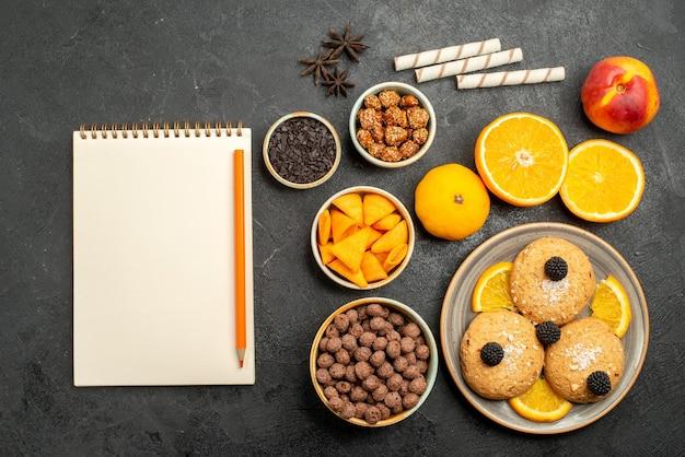Bovenaanzicht zandkoekjes met sinaasappelschijfjes op donkergrijs oppervlak, zoete fruitkoekjeskoekjes, theecake