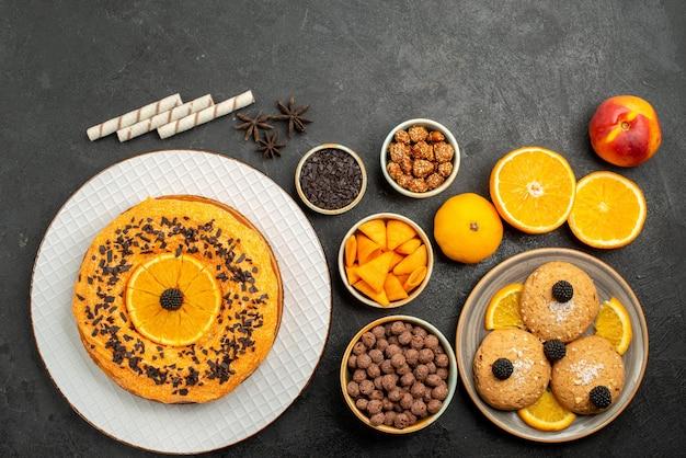 Bovenaanzicht zandkoekjes met stukjes sinaasappel en heerlijke taart op grijze oppervlakte, fruitkoekje, zoete thee