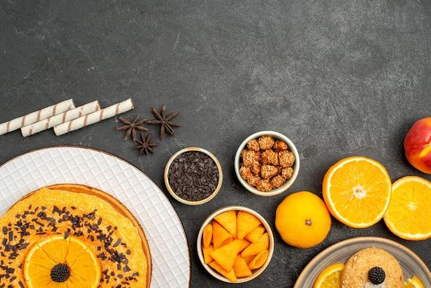 Bovenaanzicht zandkoekjes met stukjes sinaasappel en heerlijke taart op grijze oppervlakte, zoete koekjeskoekjesthee met fruitkoekjes