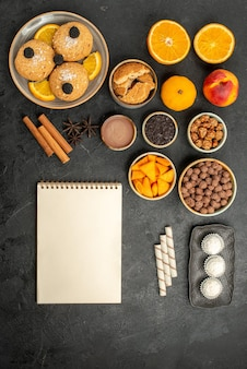 Bovenaanzicht zandkoekjes met stukjes sinaasappel en verschillende ingrediënten op een grijs oppervlak, fruitkoekje, zoete thee