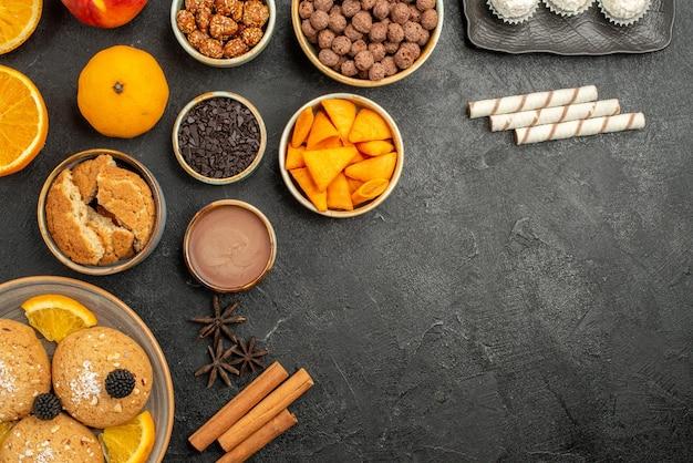 Bovenaanzicht zandkoekjes met stukjes sinaasappel en verschillende ingrediënten op grijs oppervlak, fruitkoekjes, zoete thee
