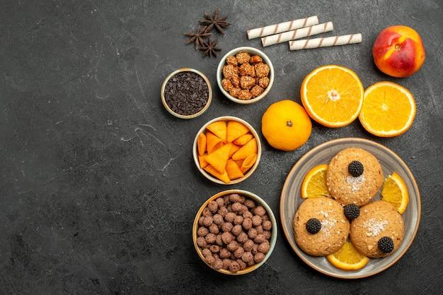 Bovenaanzicht zandkoekjes met stukjes sinaasappel op donkergrijs oppervlak, zoete koekjeskoekjesthee met fruit