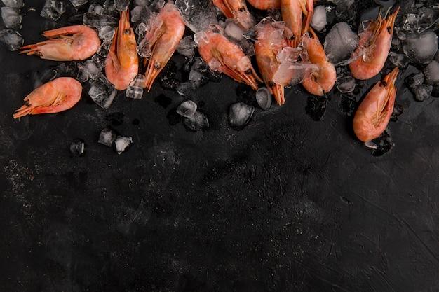 Bovenaanzicht zeevruchten garnalen op ijs kopie ruimte