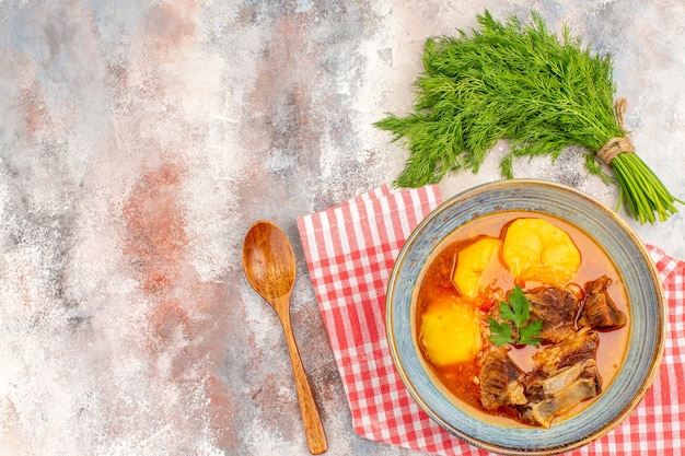 Bovenaanzicht zelfgemaakte bozbash soep keukenhanddoek een bosje dille lepel op naakt oppervlak