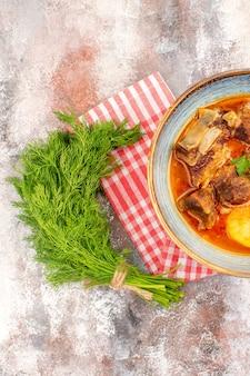 Bovenaanzicht zelfgemaakte bozbash soep keukenhanddoek een bosje dille op naakte achtergrond