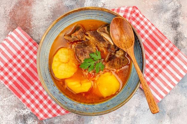Bovenaanzicht zelfgemaakte bozbash soep keukenhanddoek een houten lepel op naakt oppervlak