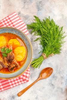 Bovenaanzicht zelfgemaakte bozbash soep keukenhanddoek een stelletje dille houten lepel op naakt achtergrond