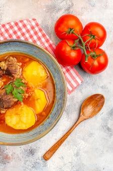 Bovenaanzicht zelfgemaakte bozbash soep keukenhanddoek houten lepel tomaten op naakt achtergrond