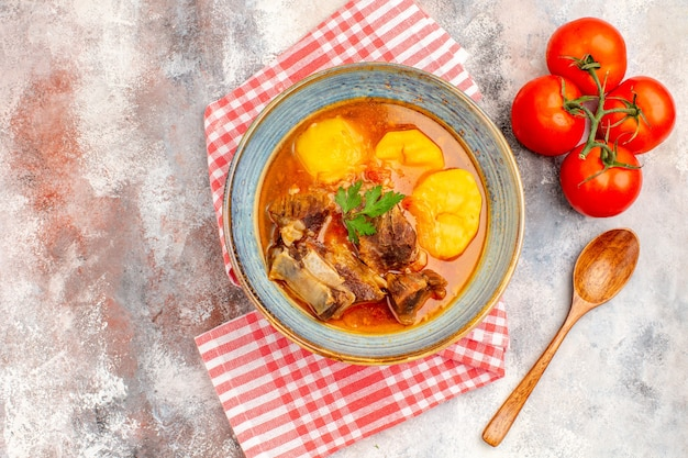 Bovenaanzicht zelfgemaakte bozbash soep keukenhanddoek houten lepel tomaten op naakt oppervlak