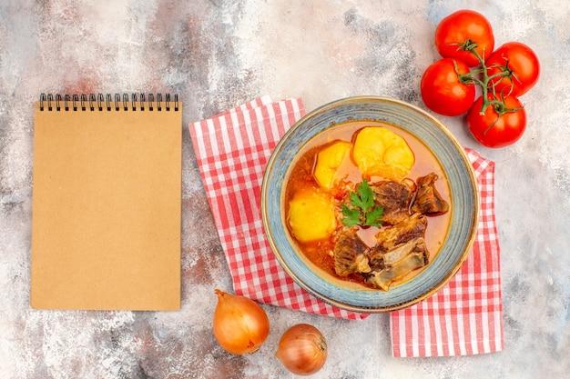 Bovenaanzicht zelfgemaakte bozbash soep keukenhanddoek uien tomaten een notitieboekje op naakte achtergrond