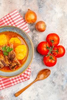 Bovenaanzicht zelfgemaakte bozbash soep keukenhanddoek uien tomaten op naakt oppervlak