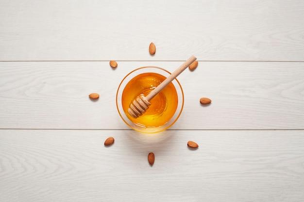 Bovenaanzicht zelfgemaakte honing omringd door amandelen