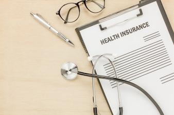 Bovenaanzicht ziektekostenverzekering vorm en bril met stethoscoop op houten background.business en gezondheidszorg concept.savings.flat lay.copy ruimte.