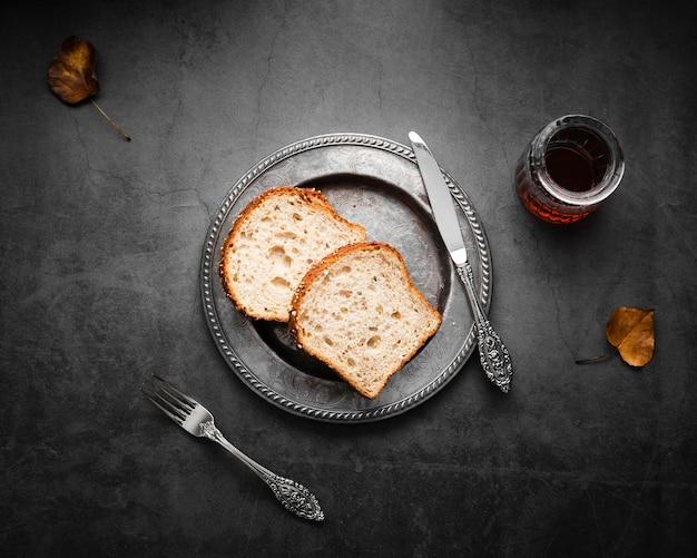 Bovenaanzicht zilveren bestek opgezet met brood en thee