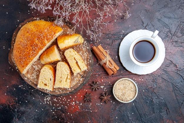 Bovenaanzicht zoet gebak in stukjes gesneden met kopje thee op donkere ondergrond