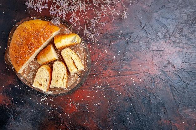 Bovenaanzicht zoet gebak in stukjes gesneden op een donkere ondergrond