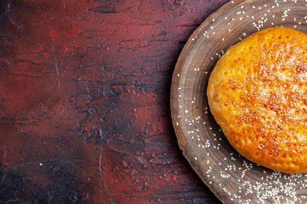 Bovenaanzicht zoet gebakken broodje brood zoals vers brood op donker bureau
