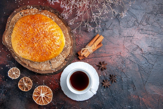 Bovenaanzicht zoet gebakken broodje met kopje thee op het donkere oppervlak
