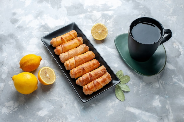 Bovenaanzicht zoete armbanden met citroen kopje thee op de lichttafel, gebak cake bakken zoete suiker