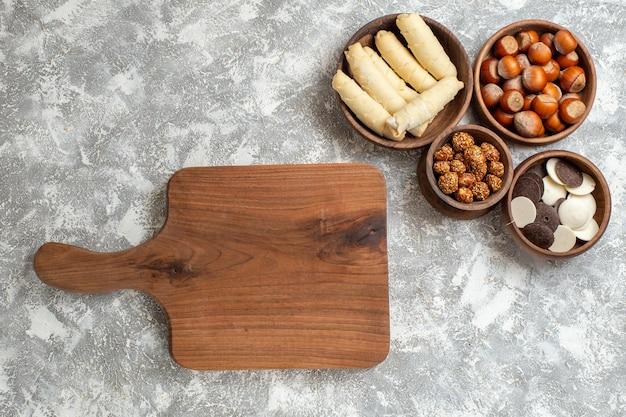 Bovenaanzicht zoete bagels met koekjes en noten op witte ondergrond