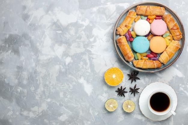 Bovenaanzicht zoete bagels met macarons en kopje thee op wit
