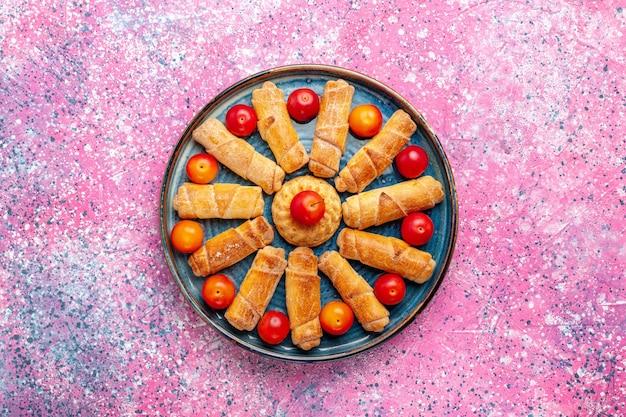 Bovenaanzicht zoete heerlijke bagels gebakken gebak in lade met pruimen op het roze bureau