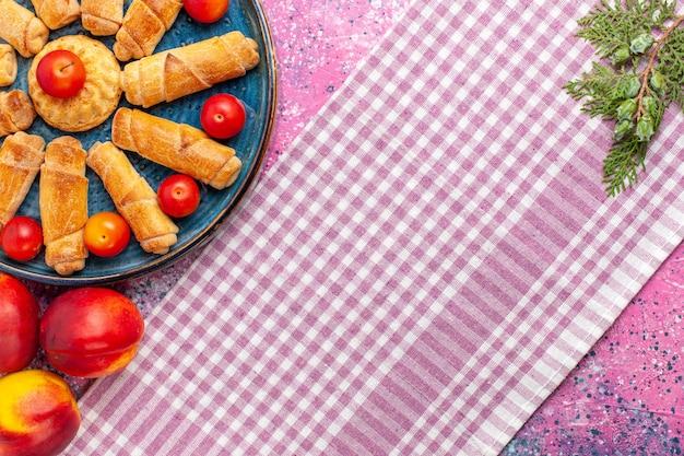 Bovenaanzicht zoete heerlijke bagels in dienblad met pruimen en perziken op lichtroze bureau