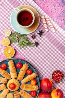 Bovenaanzicht zoete heerlijke bagels in dienblad met pruimen, verse perziken en kopje thee op lichtroze bureau