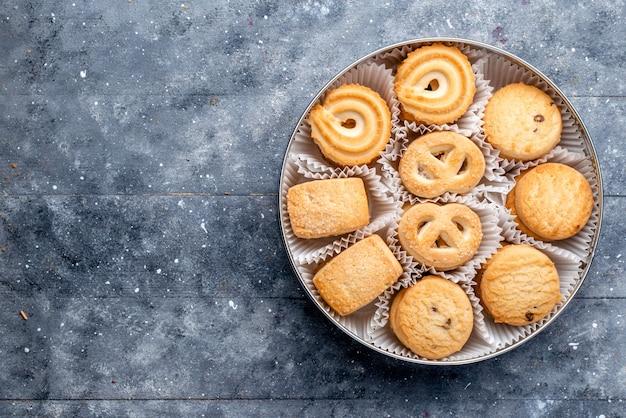 Bovenaanzicht zoete heerlijke koekjes anders gevormd binnen rond pakket op het grijze bureau zoete cake koekjeskoekje