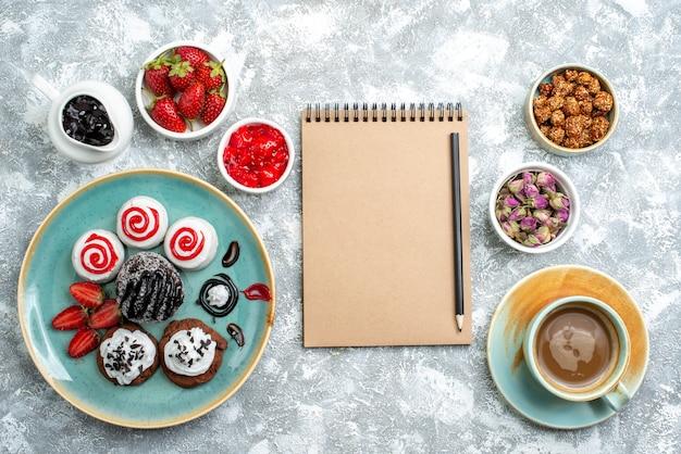 Bovenaanzicht zoete heerlijke koekjes met kopje koffie op witte achtergrond biscuit suiker cake cookie zoet