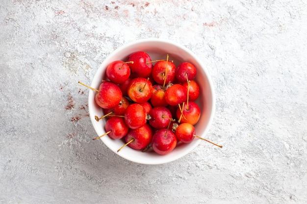 Bovenaanzicht zoete kersen vers en zacht fruit op wit oppervlak kersen fruit versheid sappig zacht