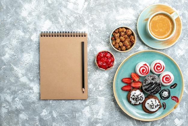 Bovenaanzicht zoete kleine cakes met kopje koffie op witte achtergrond taart cake zoete koekje suiker cookie