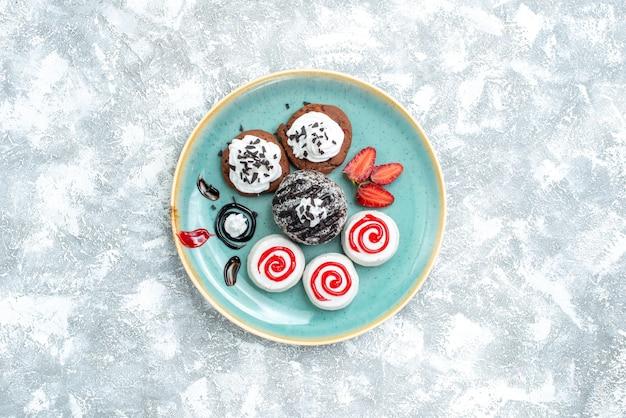 Bovenaanzicht zoete kleine cakes verschillende zoete koekjes op witte achtergrond taart cake zoete koekje koekjes suiker