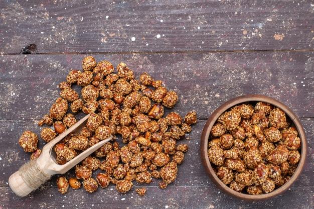 Bovenaanzicht zoete kleverige noten met honing op de houten foto van de zoete snack van de bureaunoot