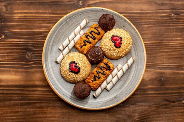 Bovenaanzicht zoete koekjes heerlijke snoepjes binnen plaat op bruine rustieke achtergrond thee koekje koekje suiker zoet